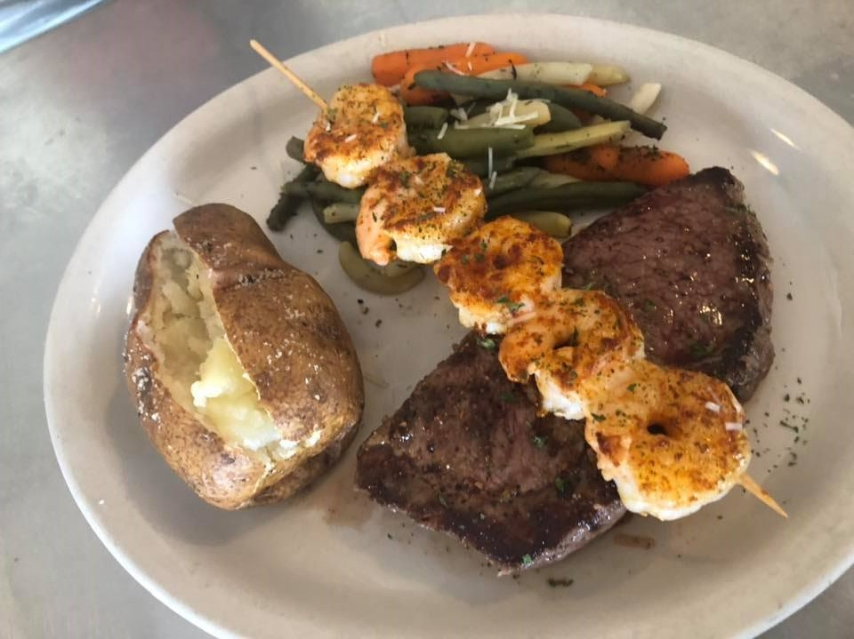 steak with shrimp, veggies, and a baked potato