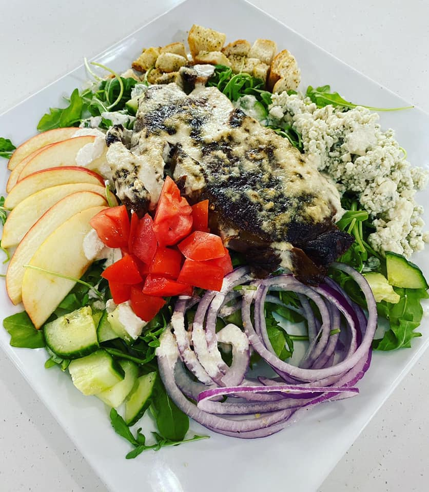 salad topped with apples, cucumbers, red onions, tomatoes, and crumbled feta cheese