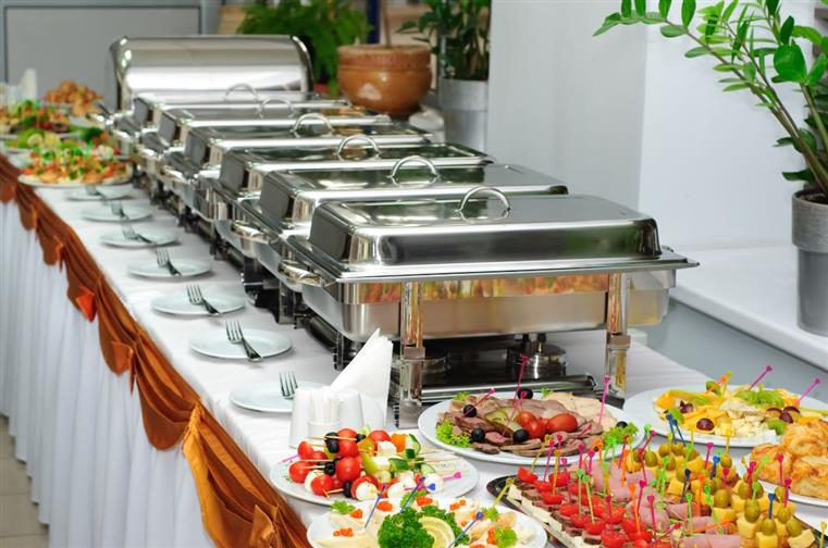 An assortment of finger foods on a table next to silver catering trays