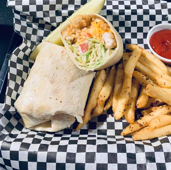 chicken wrap with lettuce, fries and pickle on the side