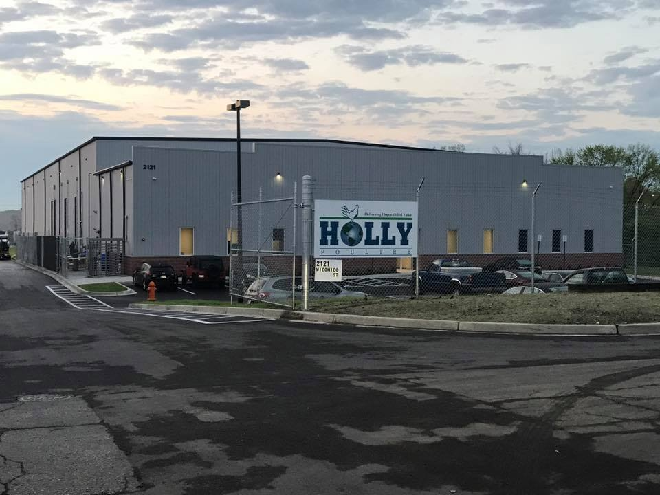 exterior of Holly Poultry warehouse  with a fence around and a Holly Poultry sign.