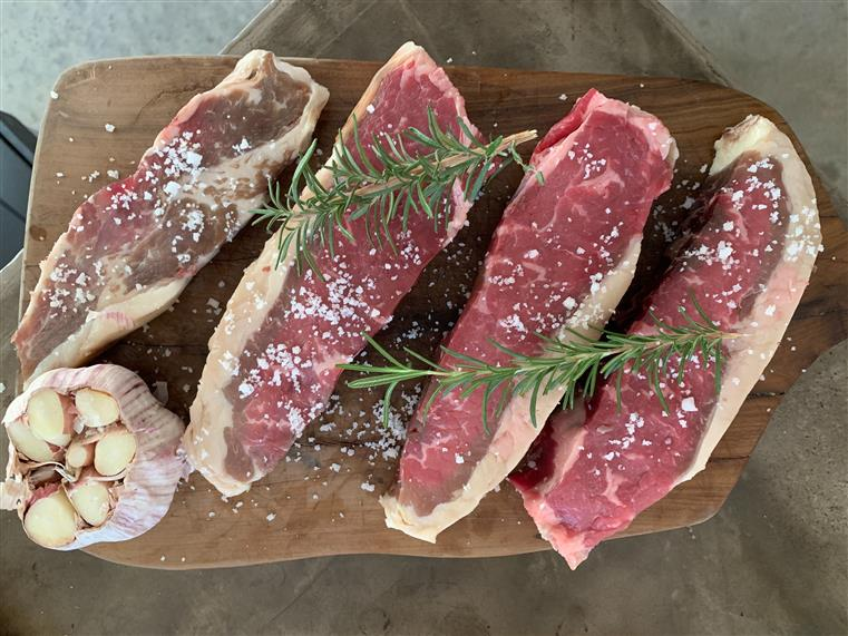 four uncooked steaks on a wood board with a head of garlic, sea salt and rosemary sprigs