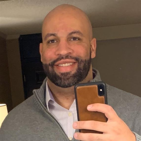 Man wearing a striped dress shirt and sweater taking a selfie in a mirror.