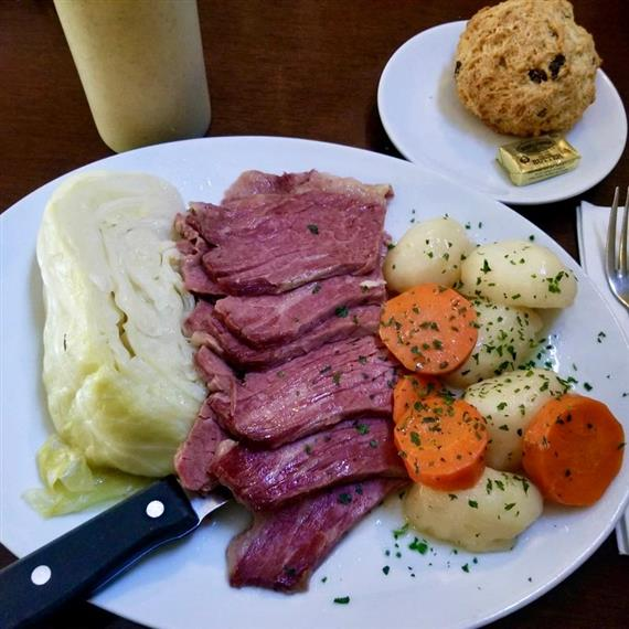 corned beef and cabbage with potatoes, carrots and soda bread biscuit on the side