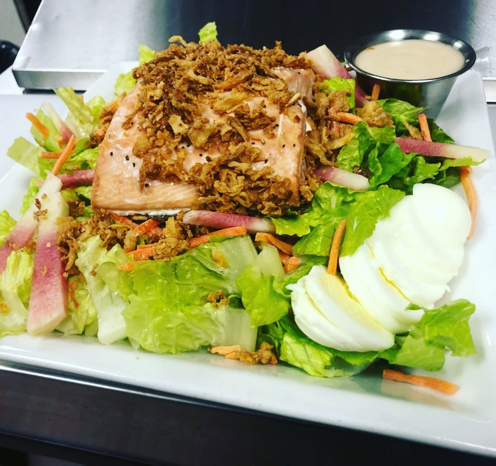 Keta Salmon Salad: Chopped romaine, crispy onions, cucumber, carrots, radish, hard-boiled egg, creamy Lemon Tahini dressing, topped with baked Keta Salmon
