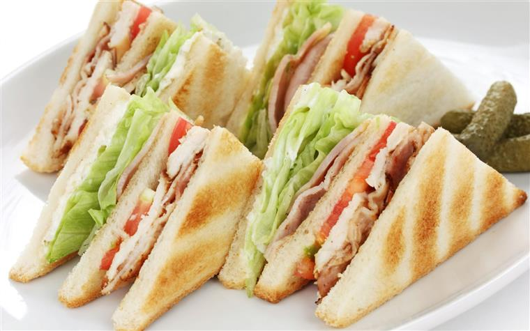 club sandwich cut into four with cornichons on the side