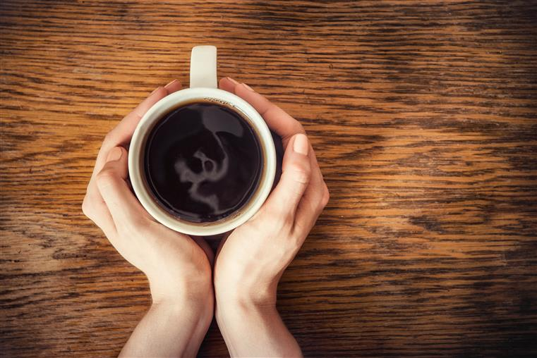 aerial view of two hands holding a coffee mug on a table