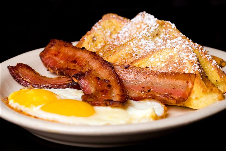 two eggs, two slabs of bacon and french toast on a plate