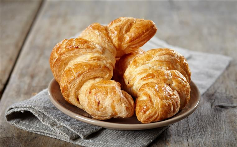 two croissants on a plate placed over a napkin