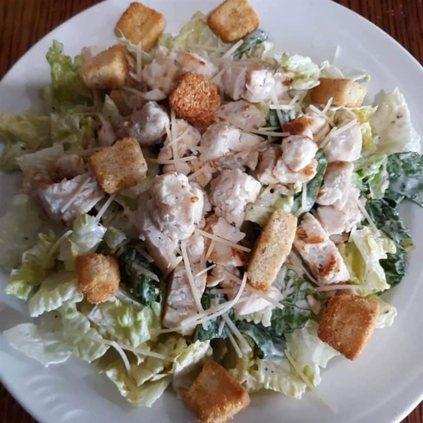 chicken caesar salad topped with cheese and croutons