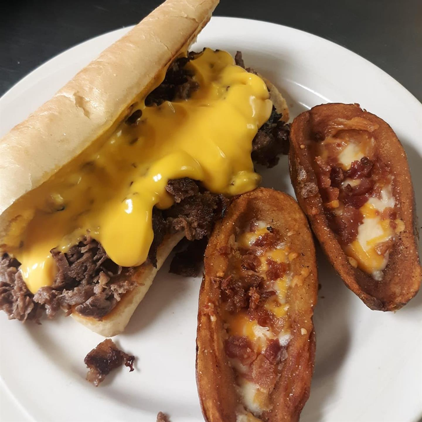 philly cheesesteak with a side of baked potatoes