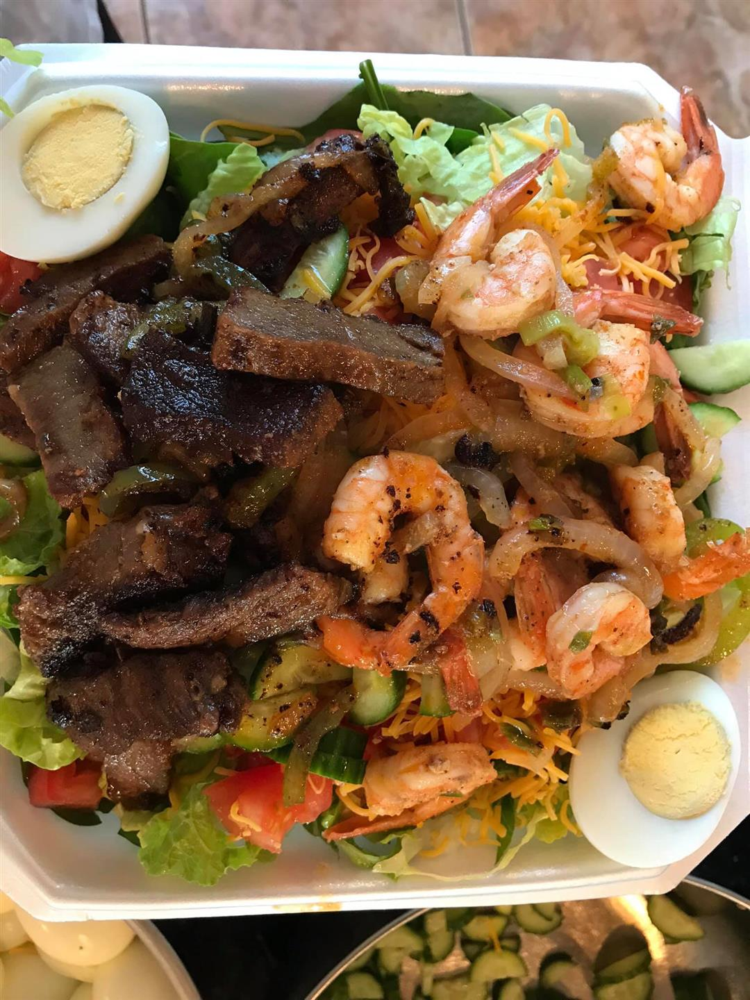 salad topped with shrimp and beef