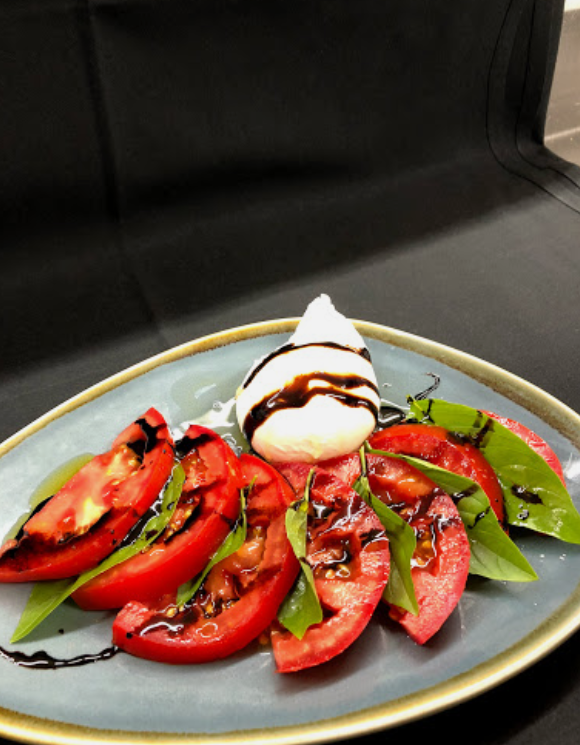 slices of tomato with basil and a side of  mozzarella cheese