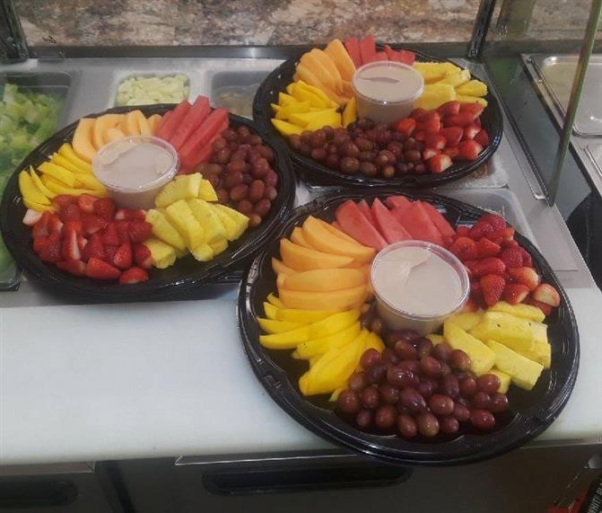 fruit trays with assorted fruit and a dipping sauce in the middle