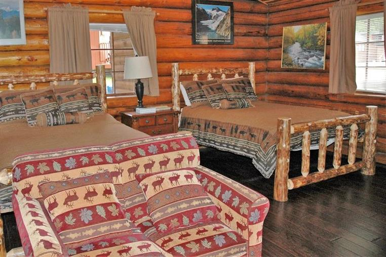 aspen log cabin indoors with two beds and a couch