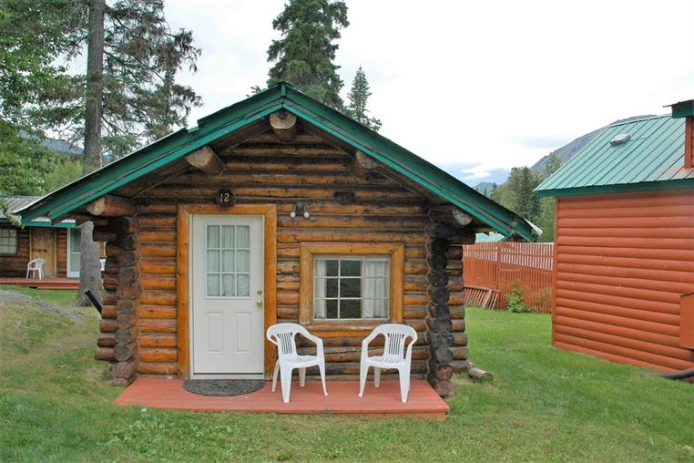 fir log cabin front entrance with two white chairs