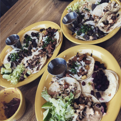 4 plates of tacos, dipping sauces, and lettuce
