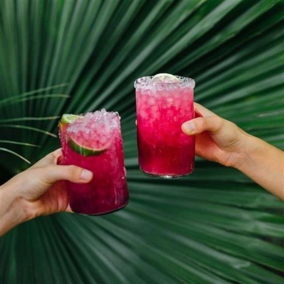 two cocktails in glass cups held by two hands