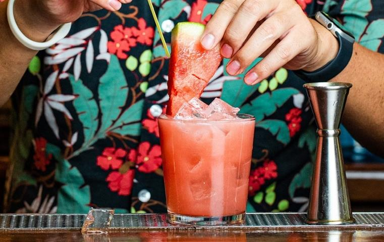 cocktail in glass cup with bartender's hand garnishing with a watermelon slice