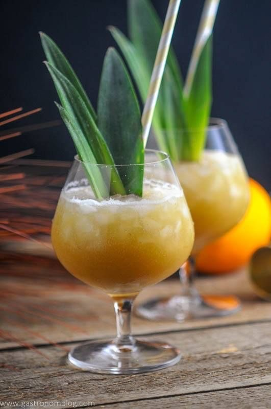 two cocktails in glass cups garnished with palm tree leaves