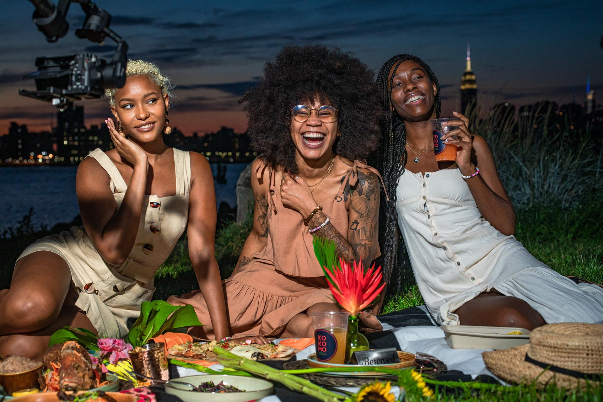 Three women smiling sitting on grass with city skyline in background and array of food in front of them.