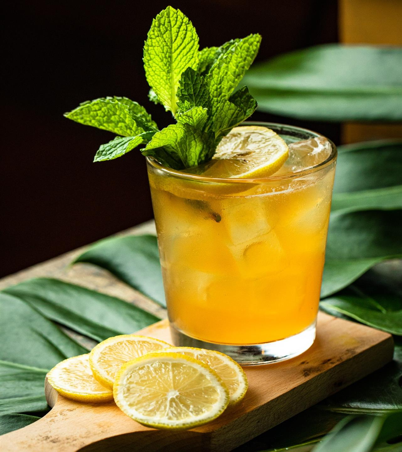 cocktail in a glass cup garnished with lemon slice and mint leaves