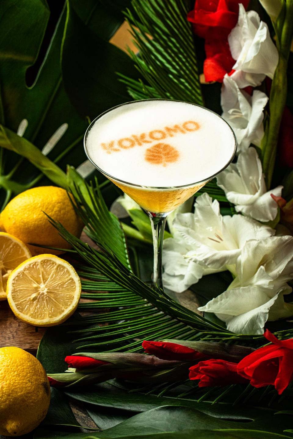 """martini glass filled with a design that says """"Kokomo"""" on the foam of drink. Lemons and flowers surround the glass"""