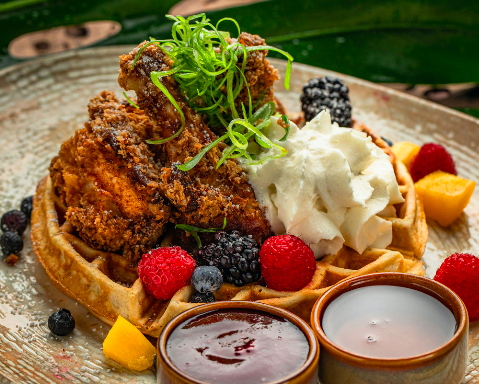 chicken and waffles with fruit, syrup and coconut whipped cream
