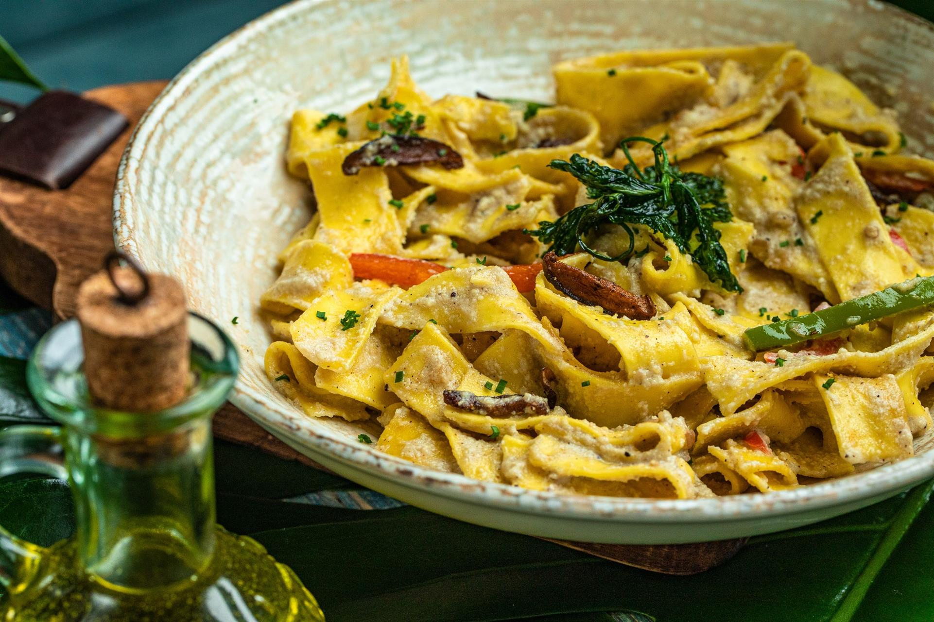 plate of pappardelle pasta, island cream sauce topped with portobello and mixed peppers.