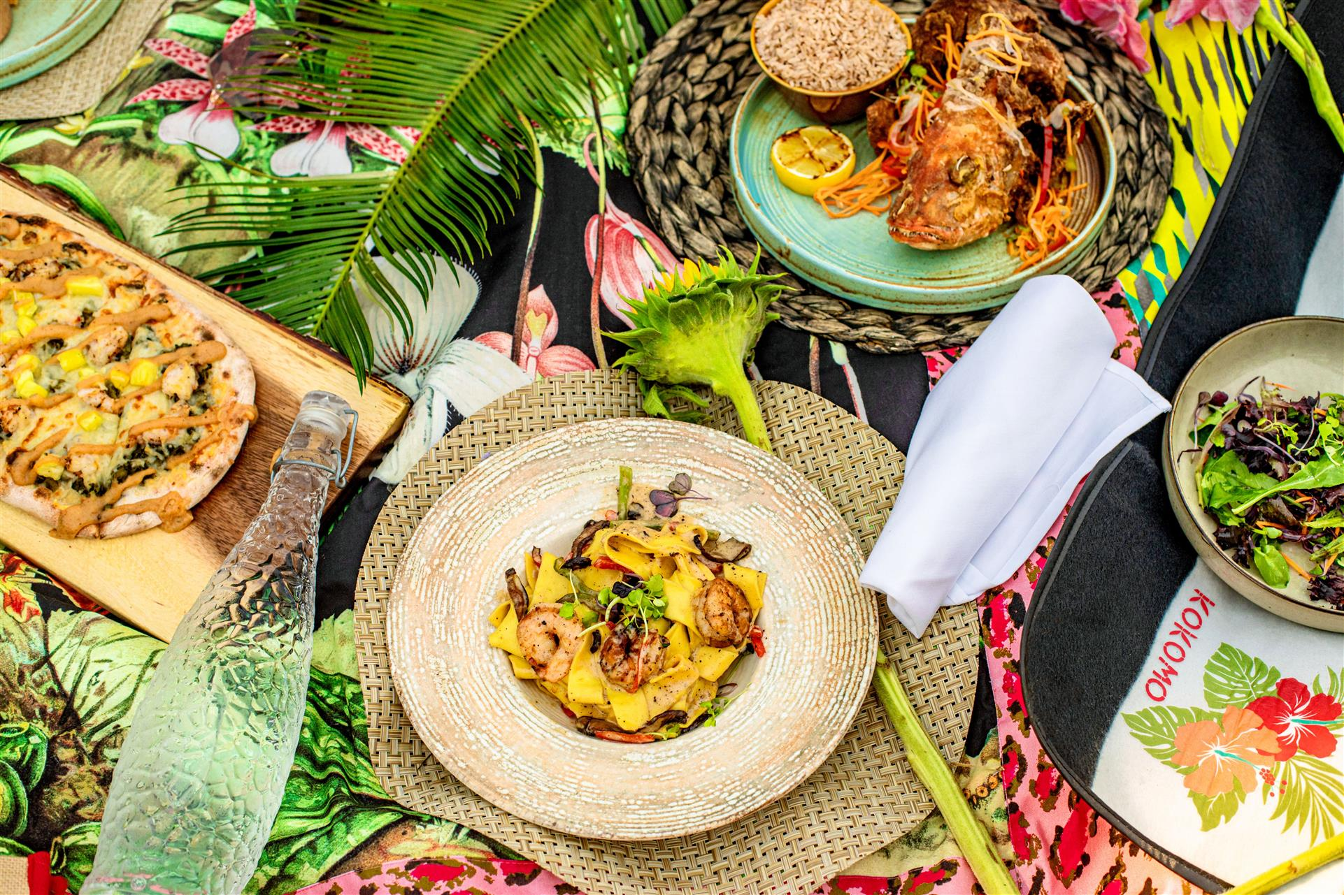 Plates of flatbread, shrimp pasta and whole fried fish with rice on dinner table with floral design table cloth and glass water bottle.