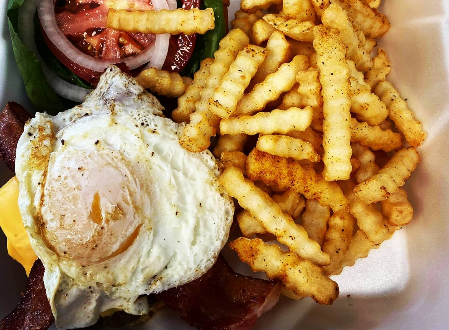 burger topped with a fried egg and served with fires
