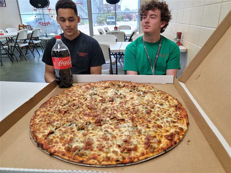 two pizza challenge contestants, with 28-inch piza and 2-liter coke