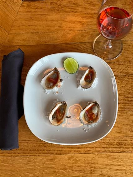 oysters with a lime wedge on a plate next to a glass of wine