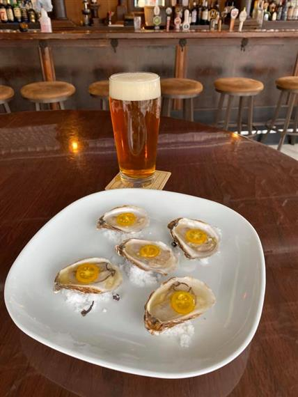 oysters on a plate with a beer