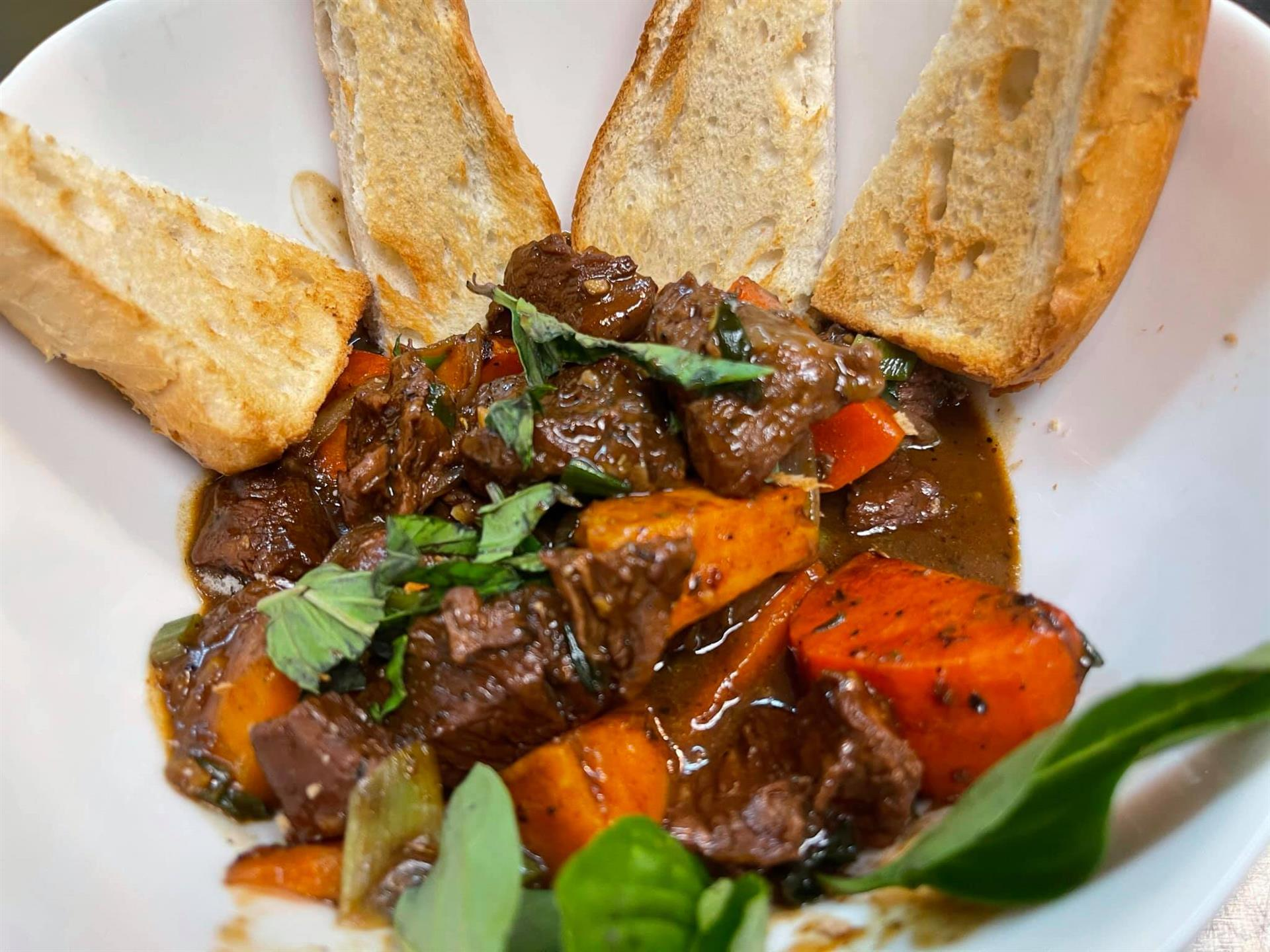 Meat with sauce, vegetables, and breadsticks