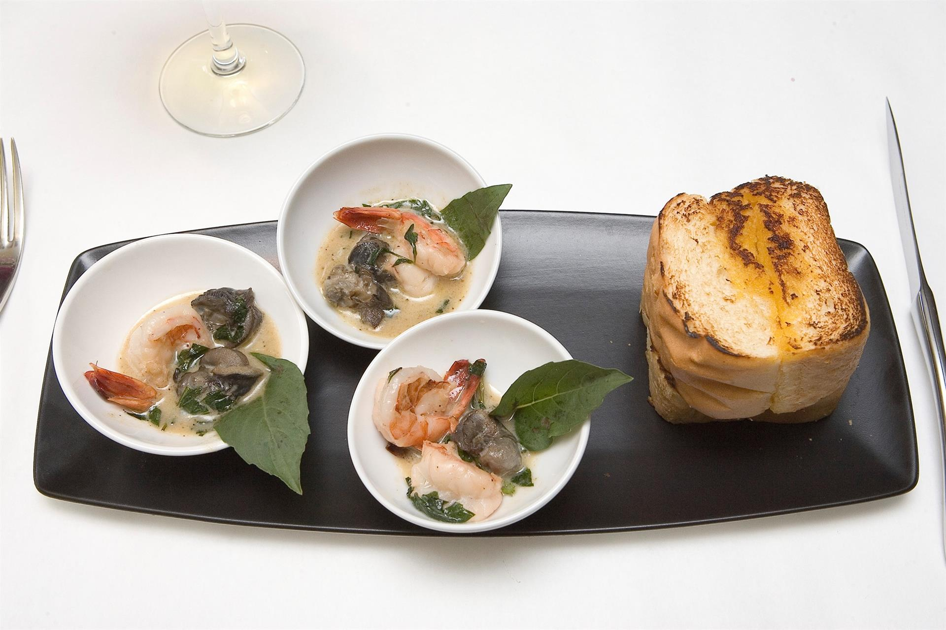 Plate of diffterent soups with side of bread
