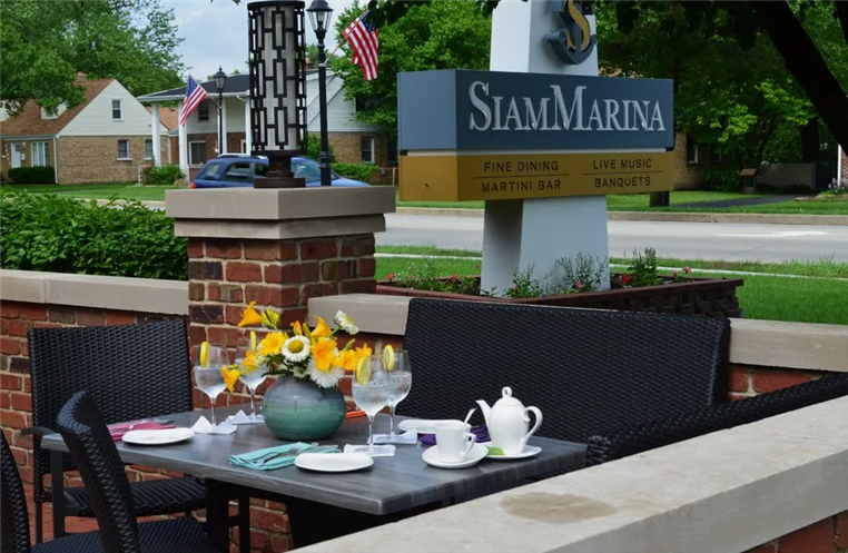 """Sign that says """"Siam Marina""""  outside with table set with flowers, tea pot and teacups"""