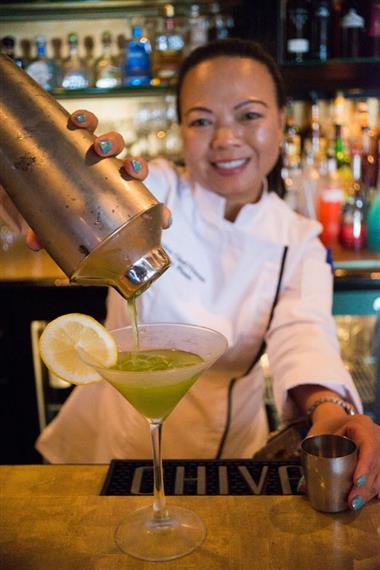 Bartender pouring drink into a martini glass