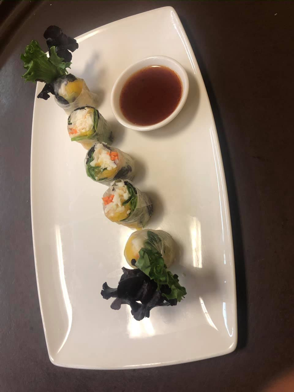 Plate of spring rolls with side of sauce