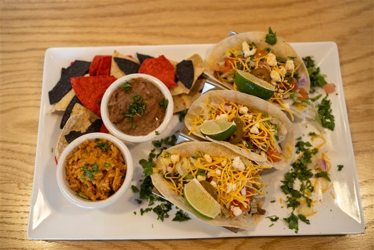 three tacos with rice, chips and beans on side