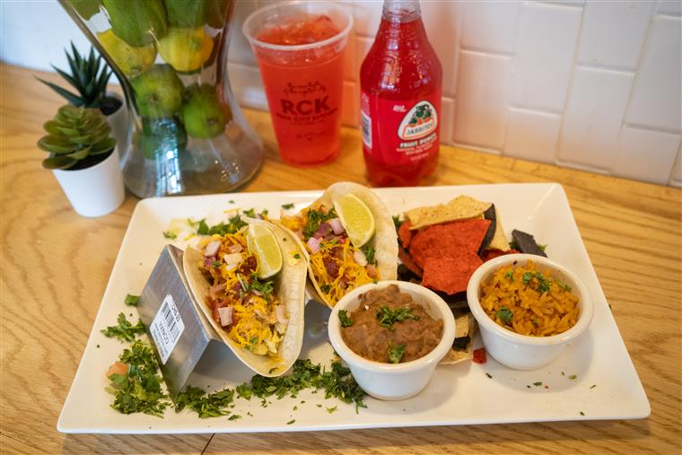 two tacos with rice and beans on side