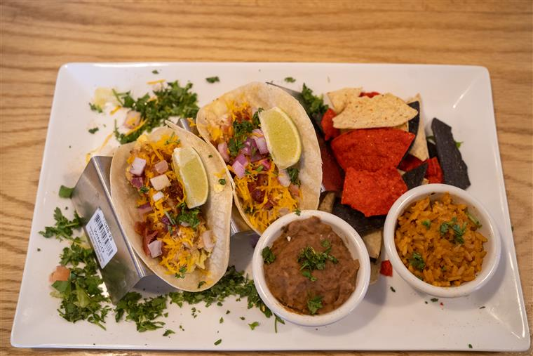 top view of two tacos with rice and beans on side