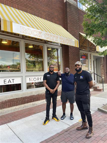 3 eople standing in front of Rock City Taco