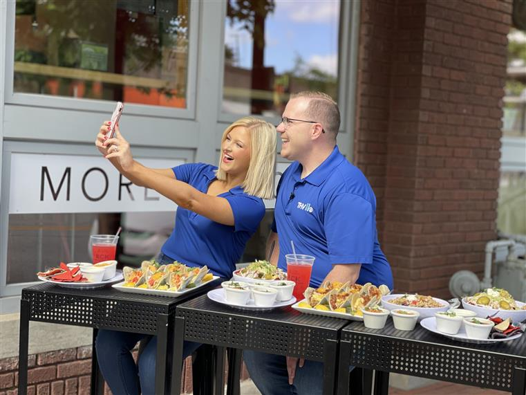 THV 11 taking a selfie with food from Rock City Taco in front of them