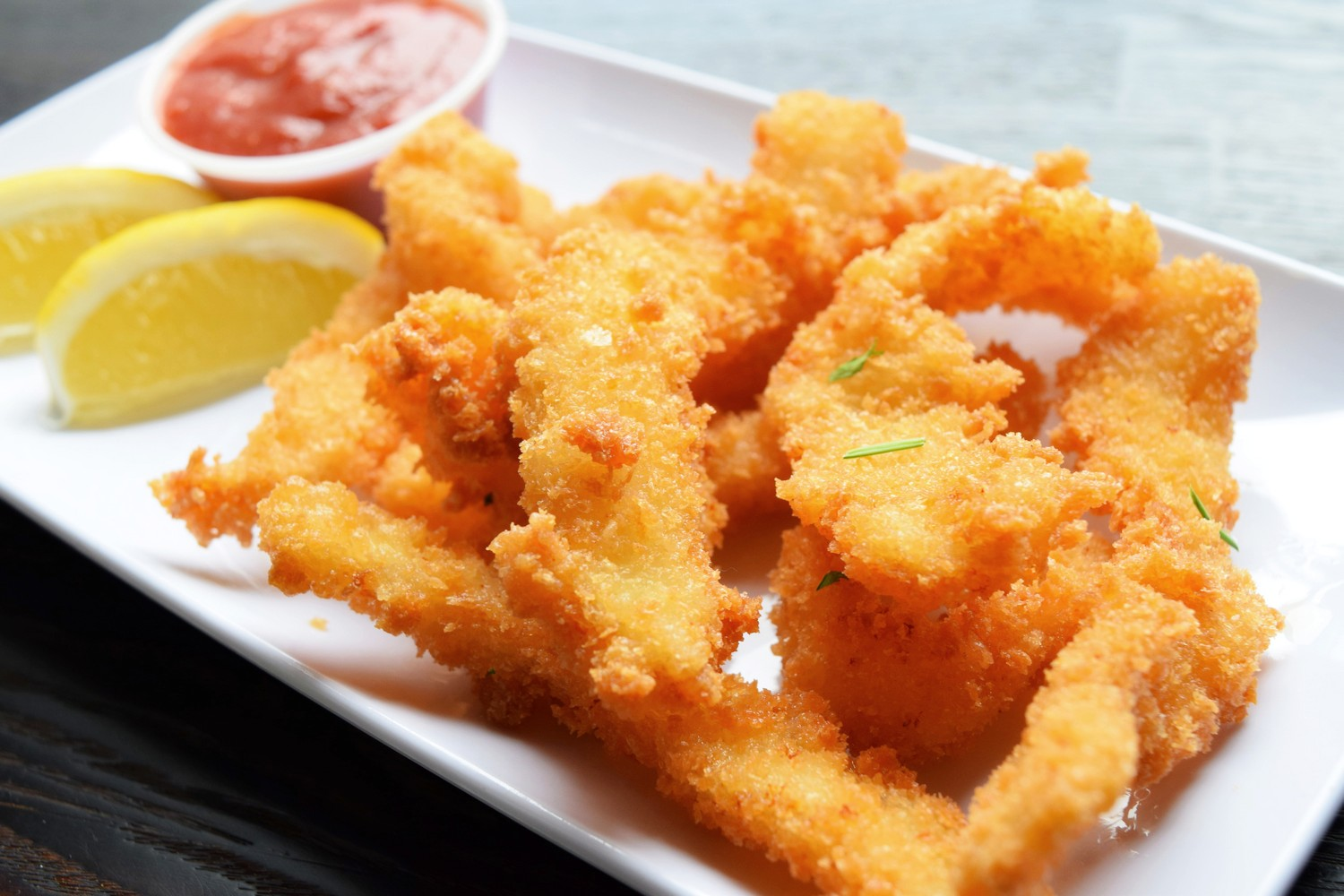 fried fish sticks with a side of dipping sauce