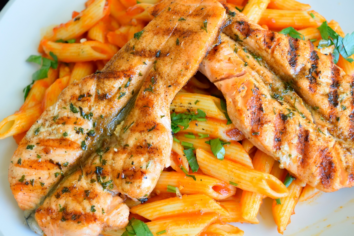 penne pasta topped with grilled chicken