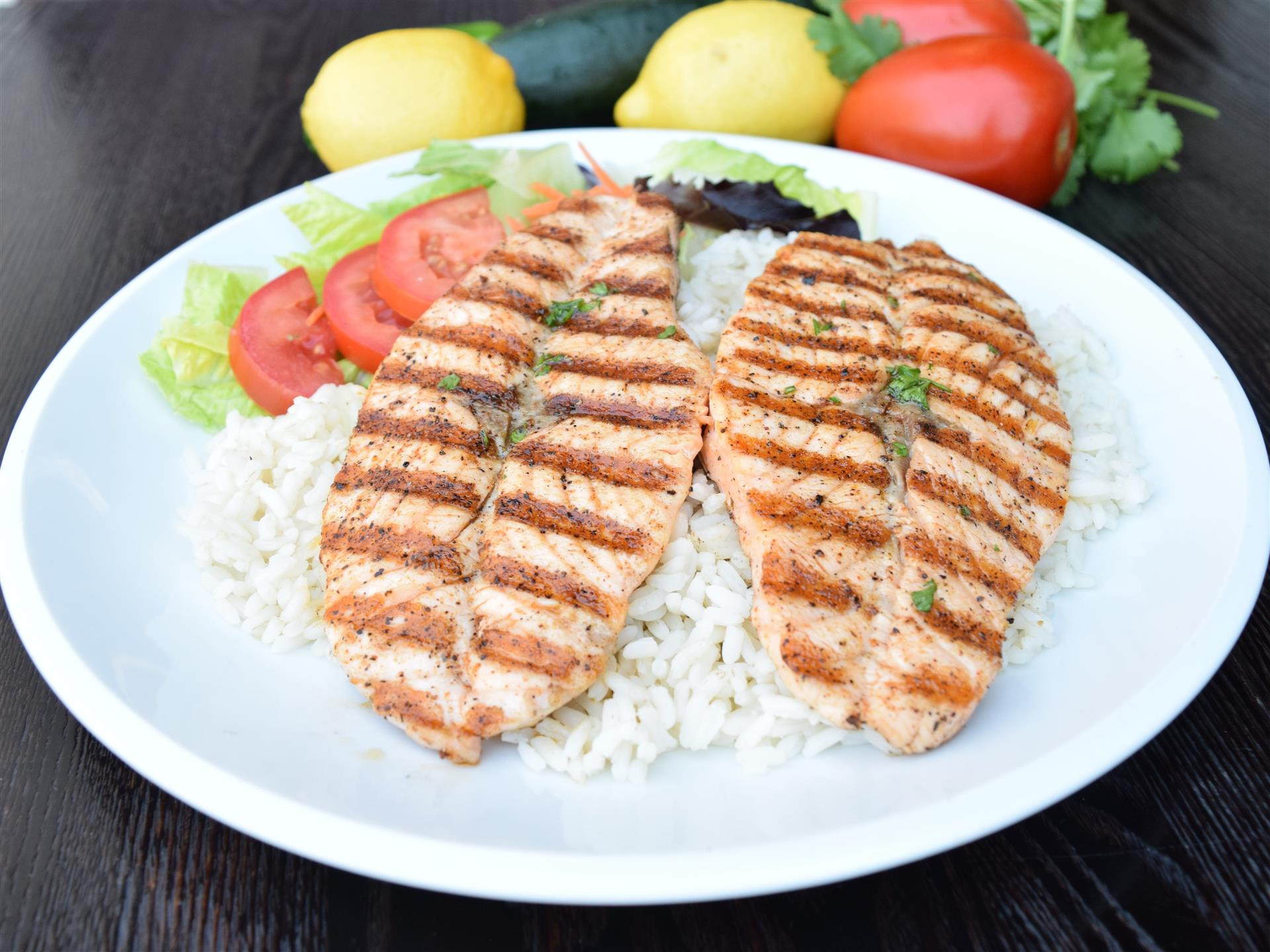 two grilled salmon filet's on a bed of rice