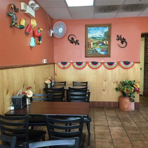 inside of restaurant with tables, chairs, and decor