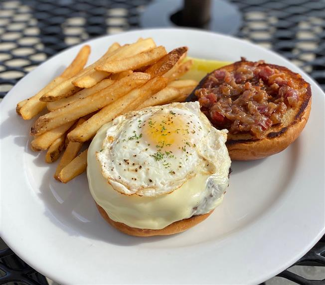 bacon cheeseburger with a fried egg and fries on the side