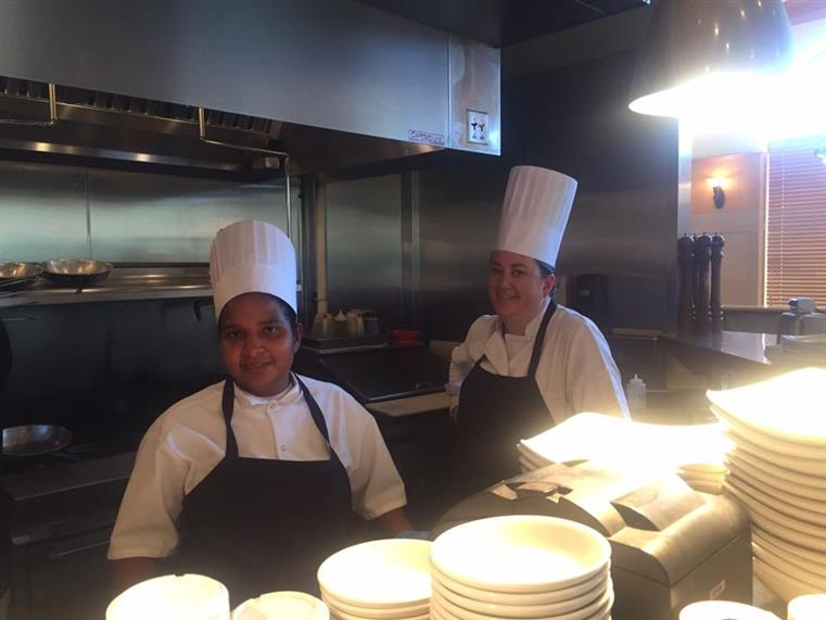 two kitchen staff in kitchen with stacks of plates